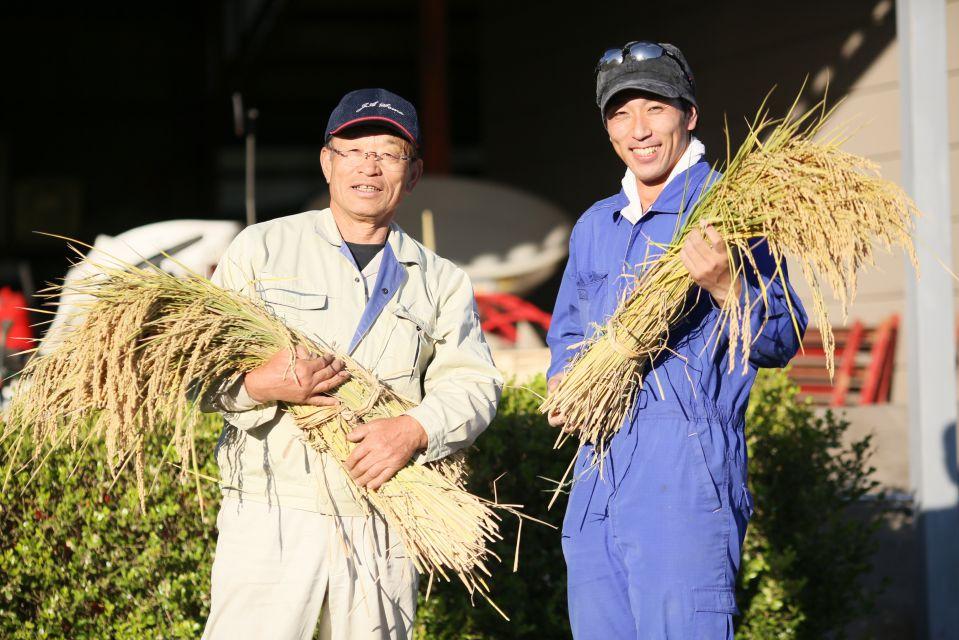 佐藤徹広さんと息子さん。収穫したお米と一緒に。